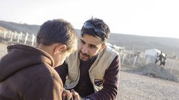 War Child staff talking to a child in Iraq