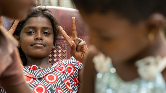 Meisje steekt vingers in de lucht vredesteken peace teken - War Child in Sri Lanka
